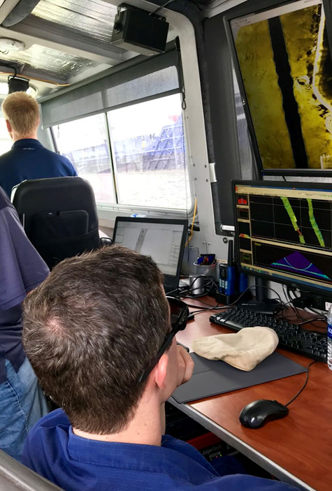 Michael Bloom drives while Lt. j.g. Patrick Lawler monitors survey acquisition. Joshua Bergeron reviews side scan data collected from the previous day looking for potential dangers to navigation.